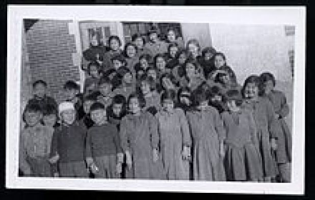 Group photo of Indigenous students in front of a brick building. A nun is visible in the back row.