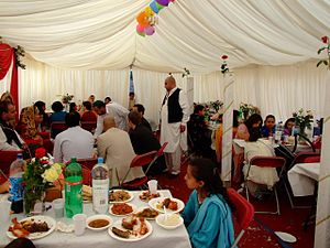 People in a marquee enjoying a wedding feast.