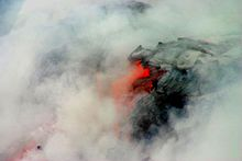 Photo showing clouds of steam surrounding lava that is partly black and partly glowing orange