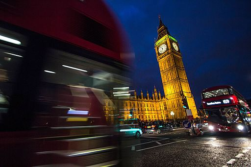 Big Ben between two London buses
