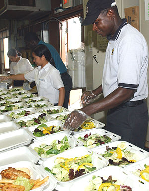 Contracted food service workers prepare meals ...