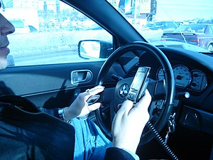 Driver in a Mitsubishi Galant using a hand hel...