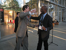 """A white man wearing a gray suit reaches to embrace Jones, while holding a book in his right hand. Jones, who is also reaching out, wears a dark suit and has a microphone and piece of paper in his left hand. Inside a glass-walled building behind them, a display says """"Climate is an angry beast and we are poking at it with sticks""""."""