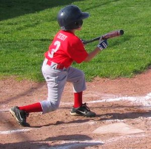 A Little League baseball player squares around...
