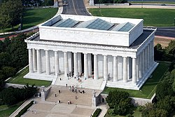 An aerial photo a large white building with big pillars.