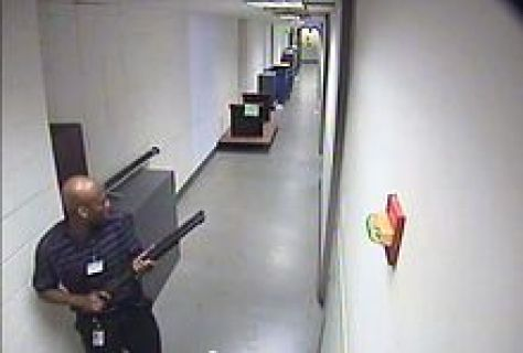 CCTV footage of the shooter in building 197 holding a Remington 870 shotgun.
