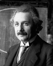 Head and shoulders photo of Einstein with moustache and graying, curly hair, smiling slightly