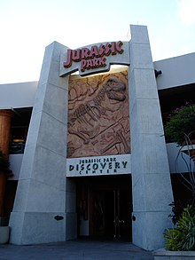 "The gateway to a facility reading ""Jurassic Park"" at the top, ""Discovery Center"" at the bottom, and a rocky panel with a Tyrannosaurus skeleton in-between."