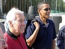Gray-haired man and Obama stand, wearing casual  polo shirts. Obama wears sunglasses and holds something slung over his  right sholder.