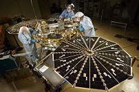 NASA's next Mars-bound spacecraft, the Phoenix Mars Lander, was partway through assembly and testing at Lockheed Martin Space Systems, Denver, in September 2006, progressing toward an August 2007 launch from Florida. In this photograph, spacecraft specialists work on the lander after its fan-like circular solar arrays have been spread open for testing. The arrays will be in this configuration when the spacecraft is active on the surface of Mars.
