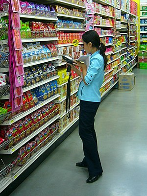 English: Female clerk doing inventory work usi...