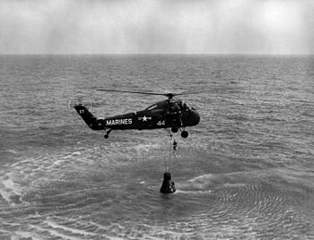 English: NASA astronaut Alan B. Shepard Jr. is hoisted up in a body harness by a U.S. Marine Sikorsky UH-34D helicopter recovery team of Marine squadron HMM-262 following the first Project Mercury suborbital space flight, 5 May 1961. Astronaut Shepard, along with his spacecraft, was then taken to the U.S. Navy carrier Lake Champlain (location: 27.23?? N 75.88?? W).