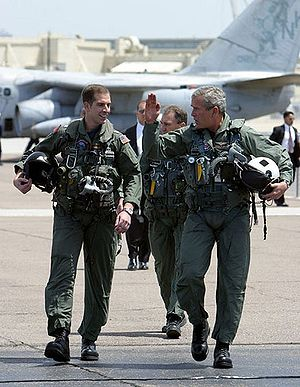 President George W. Bush walks across the tarm...