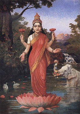 A woman wrapped in a red sari, with long hair and four hands stands on a red lotus and holds two red lotuses in her two upper hands.