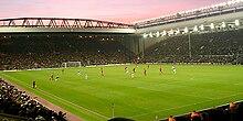 Dua berdiri dan pitch stadion sepak bola saat pertandingan dimainkan pada malam hari.