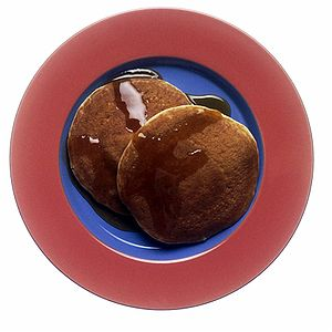 two single pancakes with maple syrup on a plate