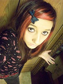 A Girl With Pink Dyed Hair Wearing Clothings Derived From