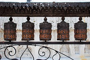 English: Rolling metal prayer wheels circling ...
