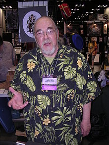 A man in his late sixties. He has a beard, glasses, and is wearing a Hawaiian shirt.