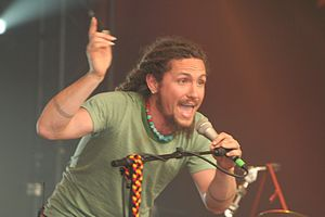 A thirty-one year-old man is shown in upper-body shot and slightly on his right profile. He is leaning forwards with his left hand grasping a microphone as he sings into it. His right arm is raised above his head and shows his long fingernails. Both fore-arms show a similar tattoo of three encircling lines. He wears an ear-ring in his right lobe, a necklace of red and blue-green beads and a green T-shirt. He is bearded and the start of his dreadlocks is visible.