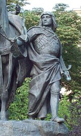 Outdoor statue of man in long cape holding a horse's reins