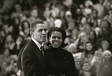 Barack en Michelle Obama, droeg Een Donkere outdoor Kleding, ten overstaan van Een menigte.  Zijn uitdrukking is gedempt;  Ze Heeft Een Brede Glimlach.