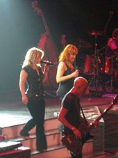 Image of two blond women walking down a step of stairs on the stage. An image of guitarist is seen standing next to them. Behind them, a set of drum and a cello are seen.