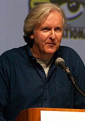 A man in a blue jacket, with a gray shirt underneath, in front of a microphone. The eye logo for the San Diego Comic-Con is seen in the background.