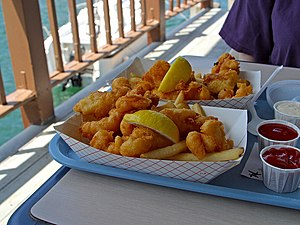 Fried fish and chips with lemon, ketchup, and ...