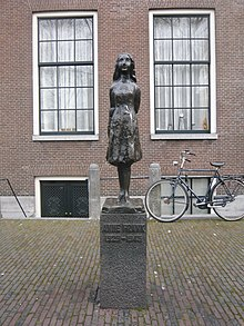 "A bronze statue of a smiling Anne Frank, wearing a short dress and standing with her arms behind her back, sits upon a stone plinth with a plaque reading ""Anne Frank 1929–1945"".  The statue is in a small square, and behind it is a brick building with two large window, and a bicycle.  The statue stands between the two windows."
