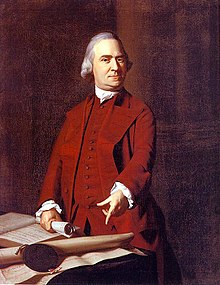 John Adams is a stern middle-aged man with gray hair is wearing a dark red suit. He is standing behind a table, holding a rolled up document in one hand, and pointing with the other hand to a large document on the table.
