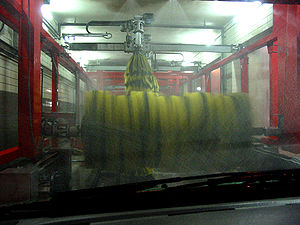 Rotating brushes inside a conveyor car-wash.