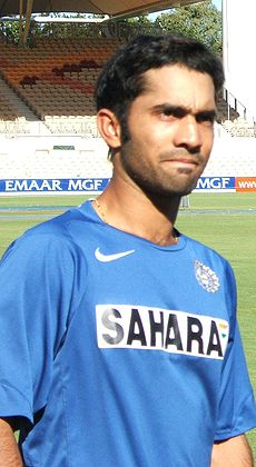 "Brown-skinned young man, not clean shaven, wears a sky blue shirt with the words ""SAHARA"" on it stares forward. In the background is lawn of a sporting ground and a grandstand."