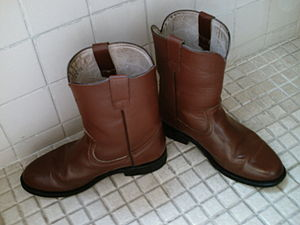 A pair of roper-style cowboy boots. Notice the...