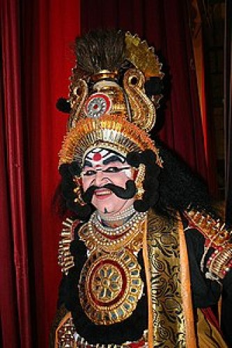 Person with painted eyes in yakshagana costume, as gold-spangled robe with red sheer scarf and spiked headress on gold crown