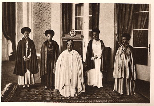 Empress Menen Asfaw seated in the center and Standing women from left to right are Princess Tsehai, Princess Tenagnework, and Princess Zenebework, her daughters, and on the far right is Princess Wolete Israel Seyoum, her daughter-in-law.