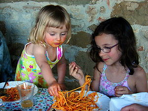 Two young girls sharing a plate of spaghetti. ...