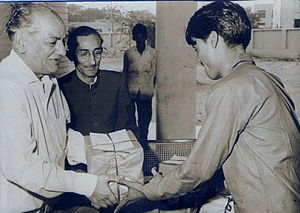 Rahman receiving the first prize from Faiz Ahm...