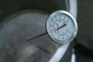 A thermometer in a bucket of heated water read...