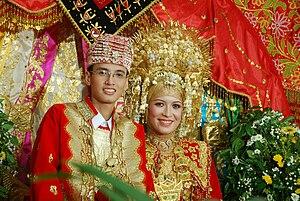 English: A Minangkabau bride and groom.