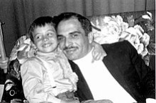 Abdullah and his father, hugging on a couch