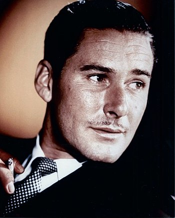 This image shows a photograph of Errol Flynn, ...