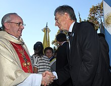 Macri shaking hands with Archbishop Jorge Bergoglio (now Pope Francis)