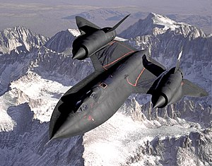 Dryden's SR-71B Blackbird, NASA 831, slices across the snow-covered southern Sierra Nevada Mountains of California after being refueled by an Air Force tanker during a 1994 flight. SR-71B was the trainer version of the SR-71. Notice the dual cockpit to allow the instructor to fly the airplane.