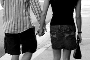 English: A male and a female holding hands.