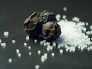 Table salt and peppercorns.