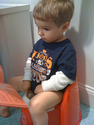A boy urinates in his potty while someone read...