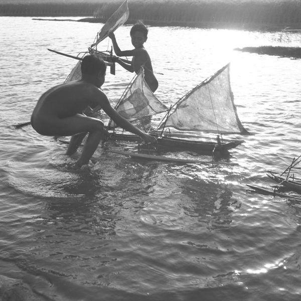 600px COLLECTIE TROPENMUSEUM Twee jongens spelen met speelgoedprauwen achter het strand bij Lebih TMnr 60030398 Mainan Bocah Belanda VS Mainan Bocah Pribumi