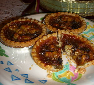 Three butter tarts on a plate, with flash