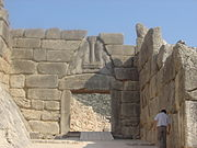 In the dry stone Cyclopean masonry of the Lion Gate of the Mycenae acropolis, the pillar flanked by lions represents the deity